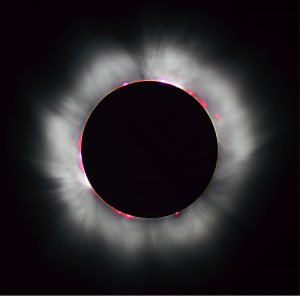 A total solar eclipse occurs where the moon completely covers the sun's disk, as seen in this 1999 solar eclipse.Solar prominences can be seen along the limb (in red) as well as extensive coronal filaments.